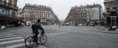 Person bicycling on a brick street in Paris