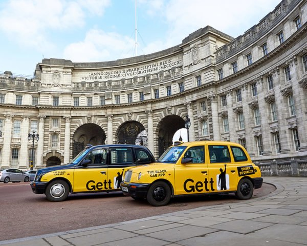 two yellow and black taxis in front of Admiralty Arch in London