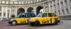 cropped close-up of two yellow and black taxis in front of Admiralty Arch in London