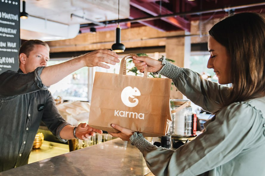 person picking up brown paper bag with karma logo on it from a restaurant