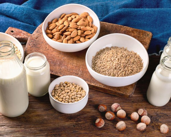 Glass jars of milk and bowls of nuts, rice and oats