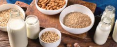 cropped close-up of glass jars of milk and bowls of nuts, rice and oats