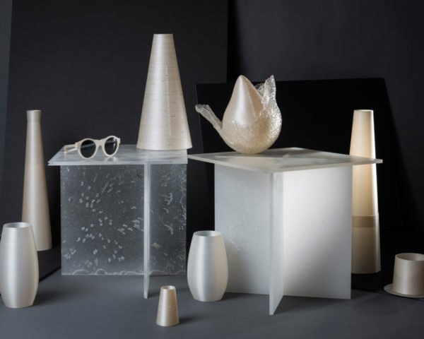 Vases, tables and sunglasses made from bioplastic on dark background