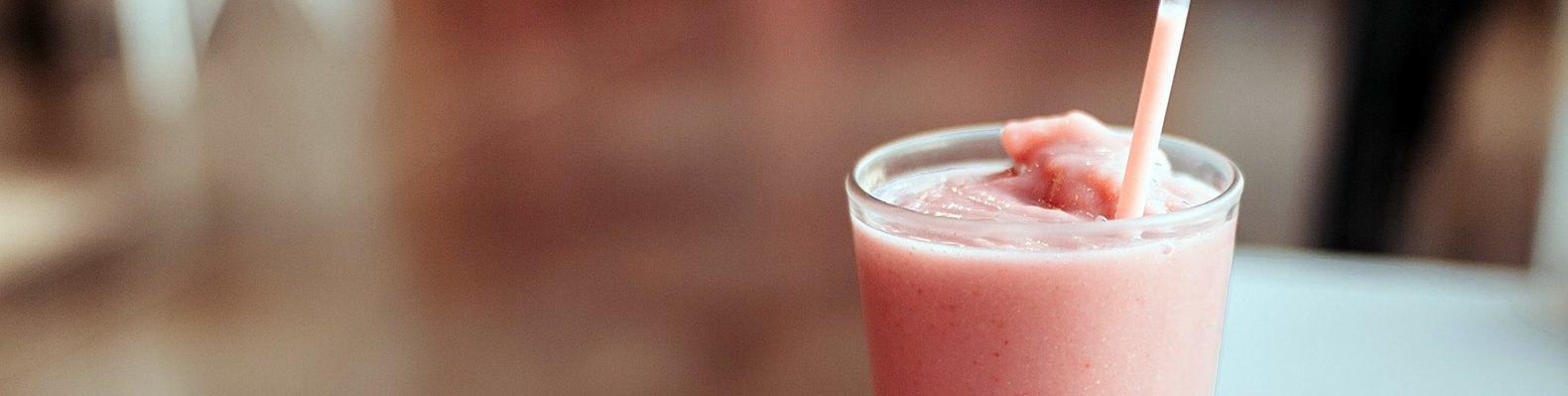 cropped close-up of strawberry milkshake in glass cup with plastic straw on a table