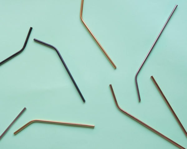 different colors of metal straws on light blue background