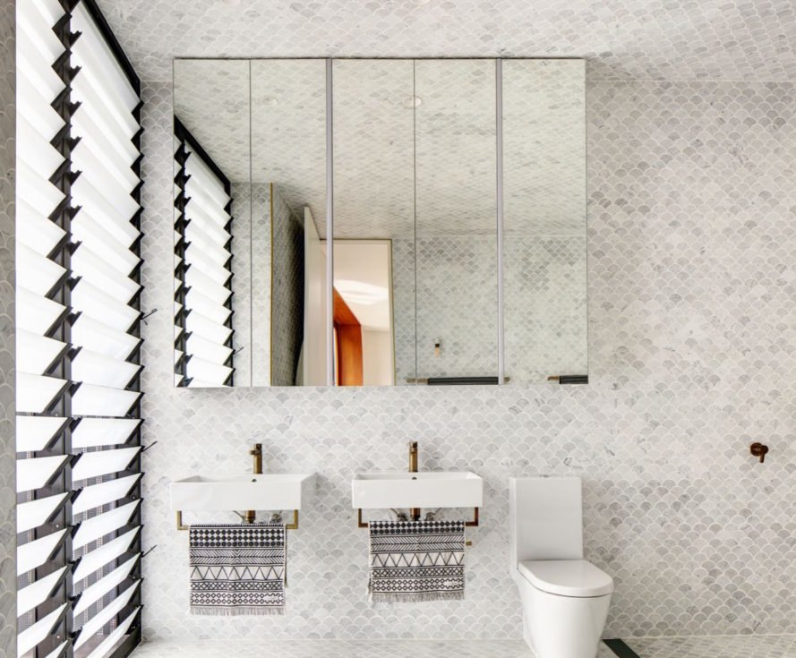 bathroom with gray scalloped tiles and modern white sinks with brass fixtures