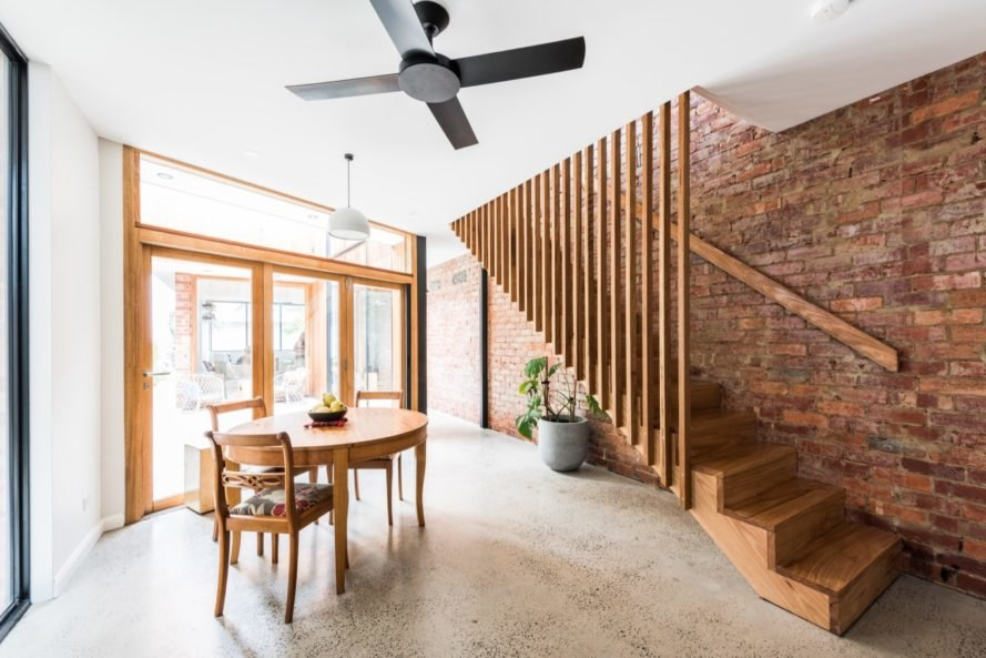 dining area with wood table, wood stairs and an exposed red brick wall