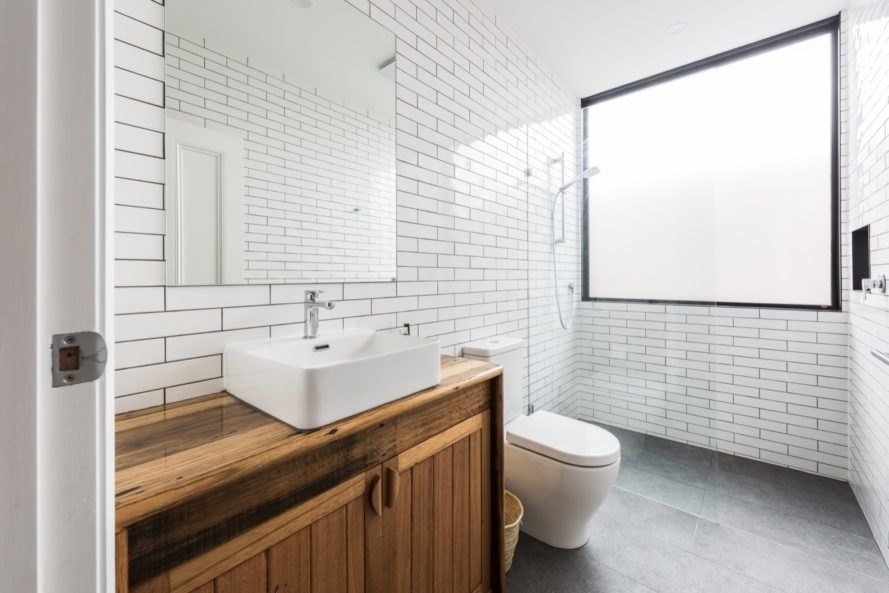 white bathroom with subway tile, gray floors and a timber counter