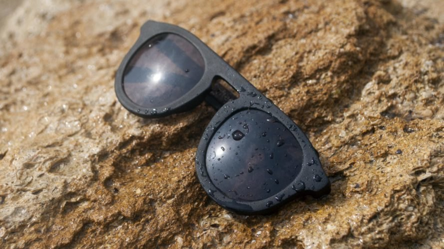 a pair of black sunglasses on a rock splattered with water