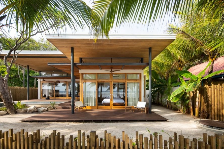 a horizontal beach home with extended roof surrounded by palm trees