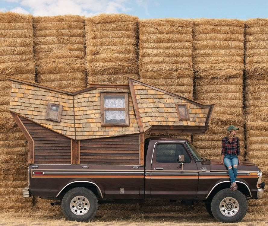 truck with wooden cabin on the truck bed in front of hay