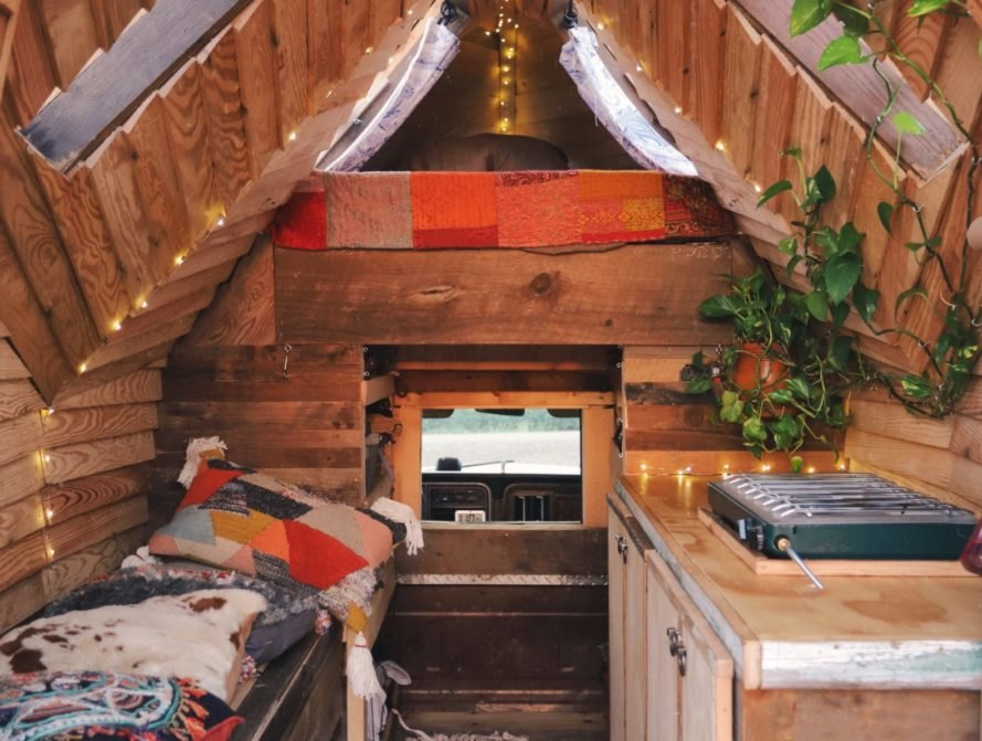 wooden sleeping space with a lofted bed and kitchen