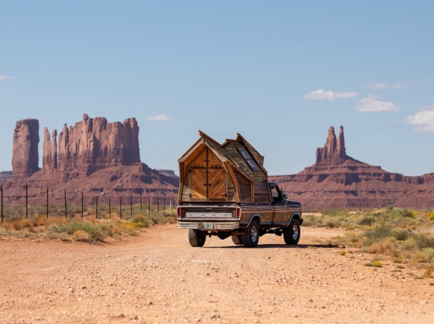 truck with wooden cabin on the truck bed driving toward mountains