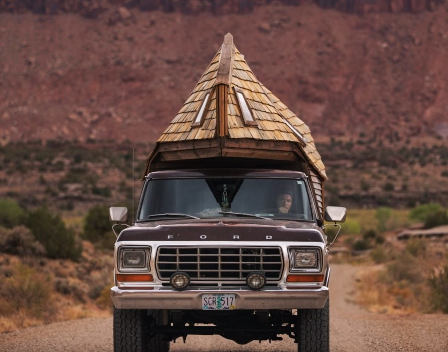 man driving a truck with wooden cabin on the truck bed