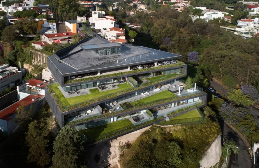 aerial view of apartment with multiple green roofs