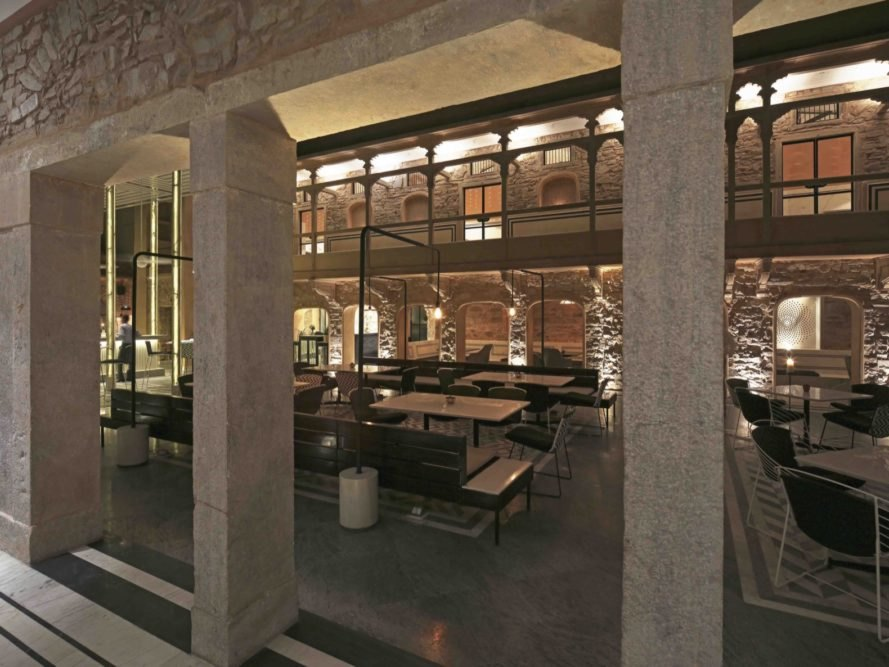new restaurant with restored stone walls and open-air dining space with marbled floors