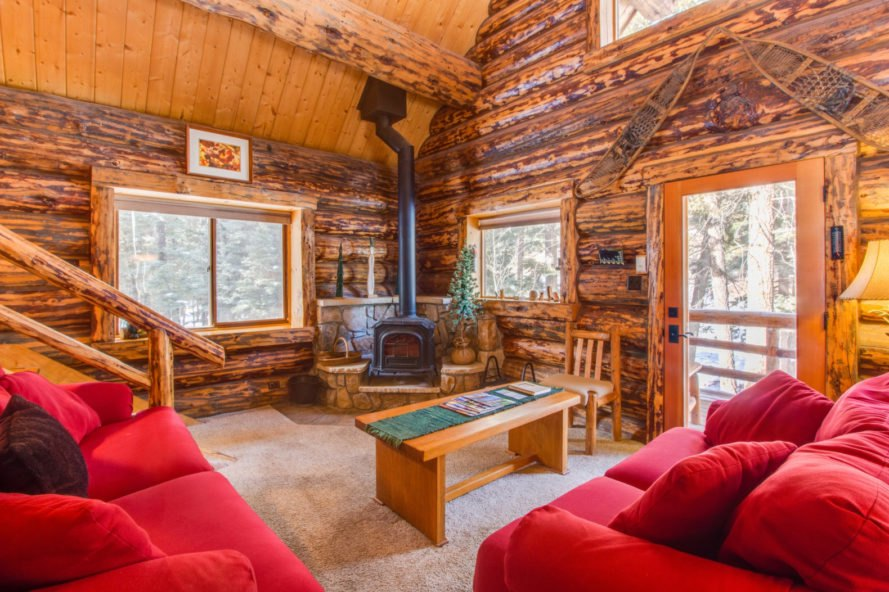 interior living room in log cabin with red furniture facing wood-burning stove