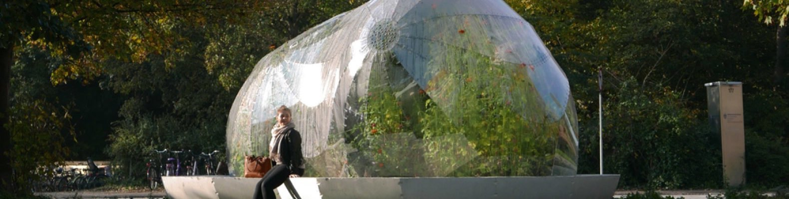 bubble-like dome filled with plants and woman sitting beside it