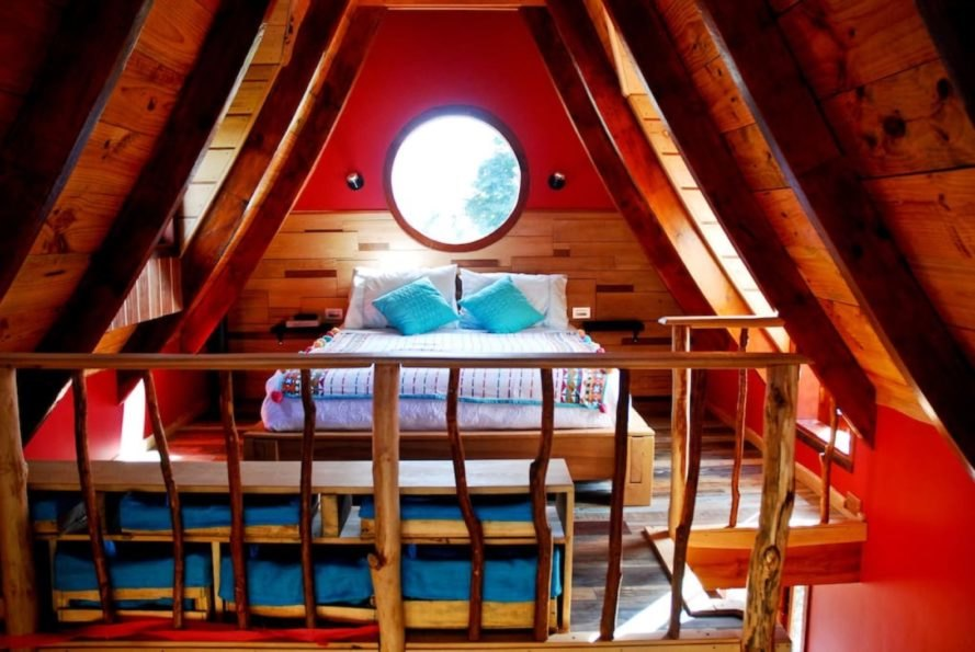 timber-lined bedroom with round window