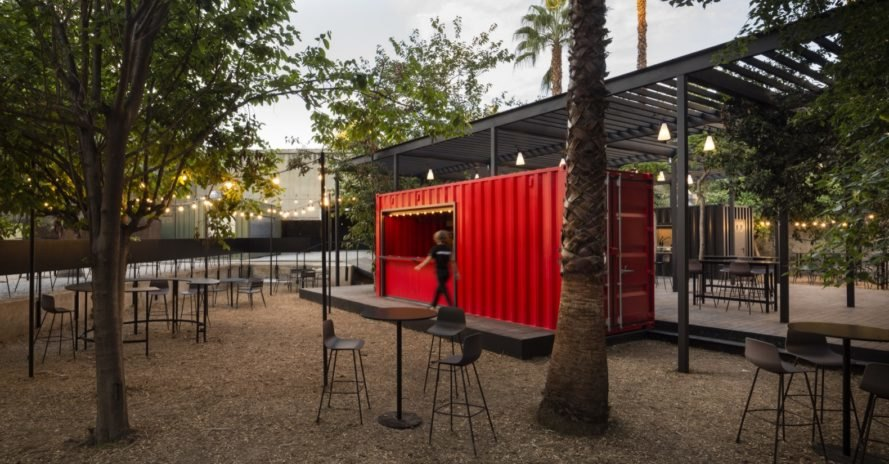 bright red shipping container surrounded by dining tables and chairs