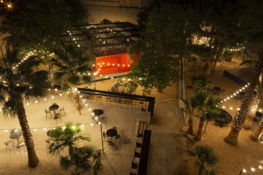 aerial view of outdoor dining area with palm trees, black tables and chairs, twinkle lights and a red shipping container