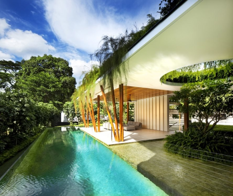 white and wood home with green roof and a pool