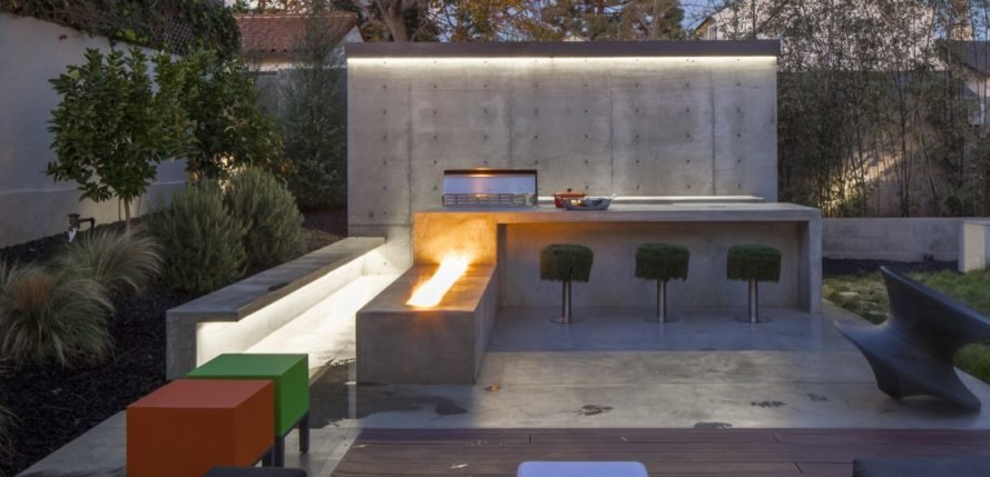 outdoor kitchen with grass-covered barstools and concrete fire pit