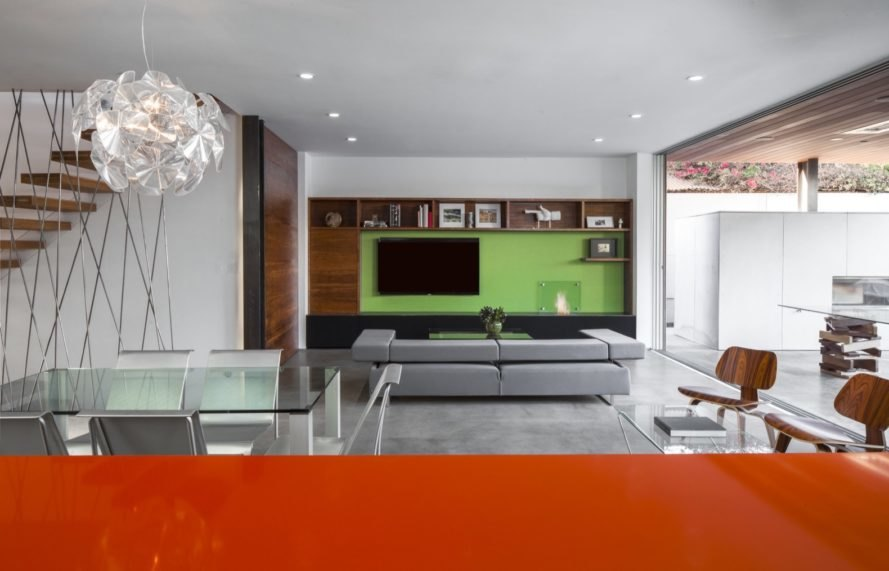 glass dining table with gray couch and green entertainment center in background