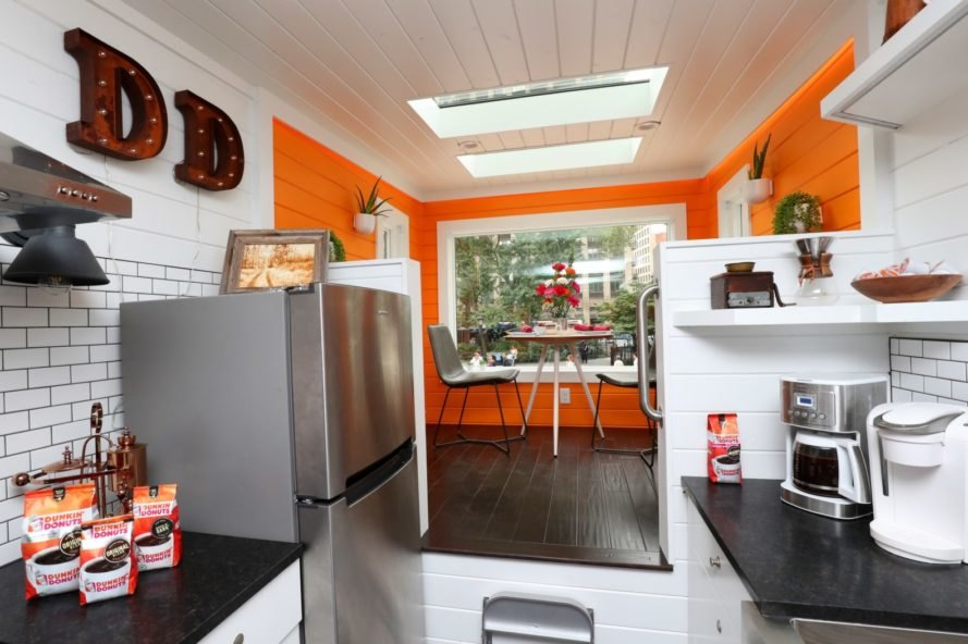 white kitchen space with elevated orange dining area