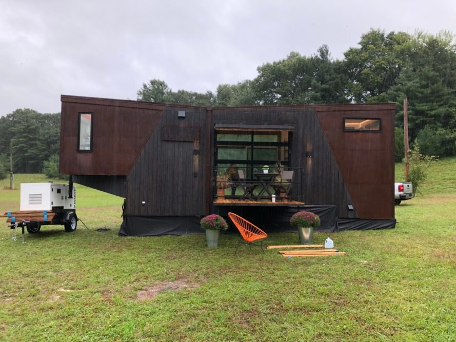 a tiny home with dark wood and black cladding on grassy lot