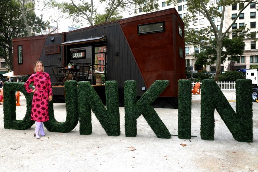 green lettering spells out Dunkin in front of a tiny home