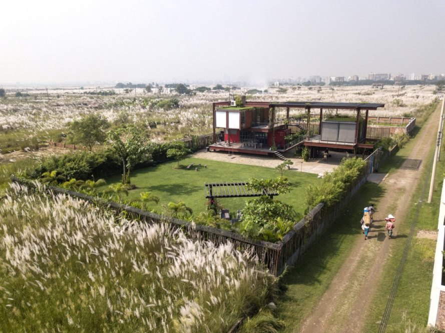 aerial view of red shipping containers topped with a green roof