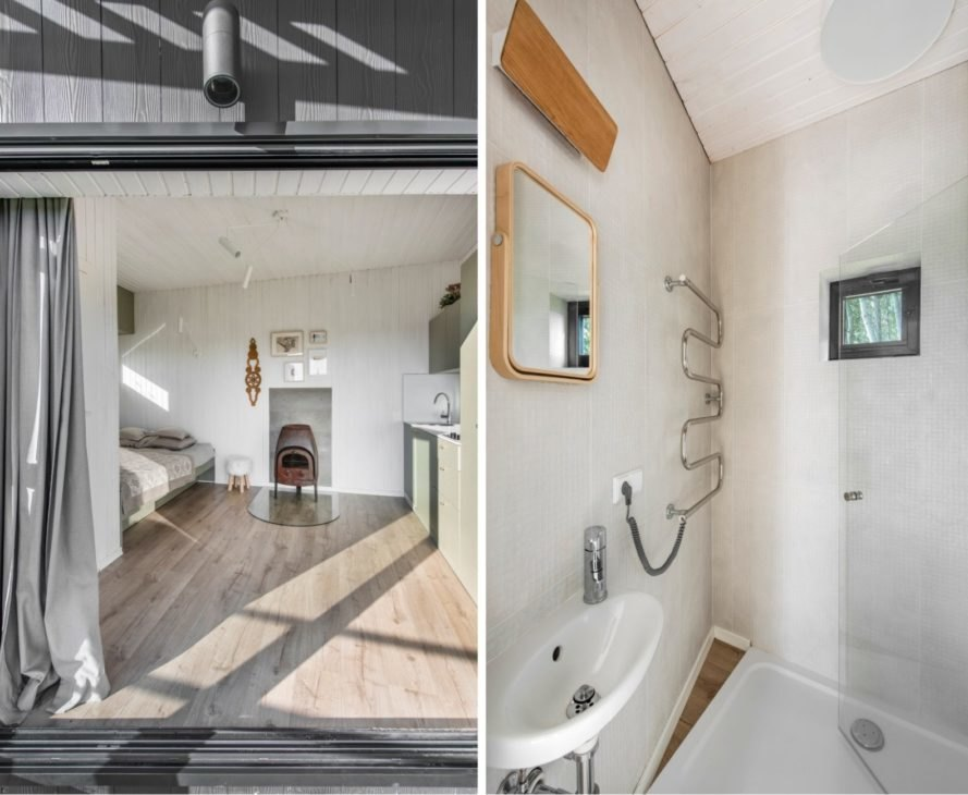 On the left, white room with tan bed and wood-burning stove. On the right, white bathroom with small wood-framed mirror.