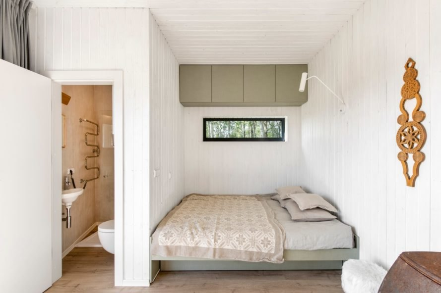 a bedroom with white walls and tan bedding