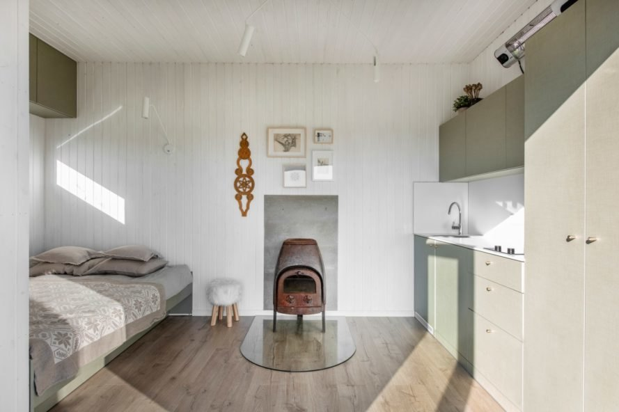 white room with bed, wood-burning stove and small kitchen