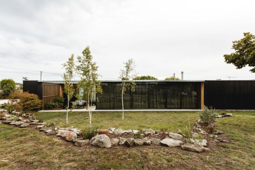 one-story black timber home facing a garden