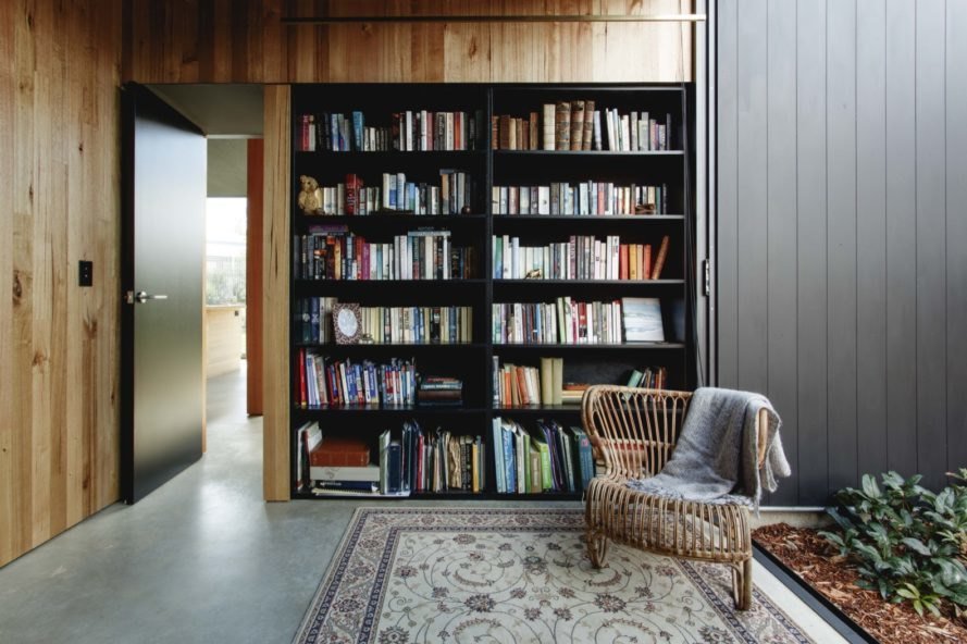 built-in black bookshelves filled with books near a wicker chair