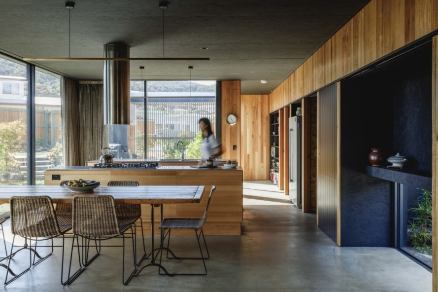 timber-lined kitchen with glass walls and timber island