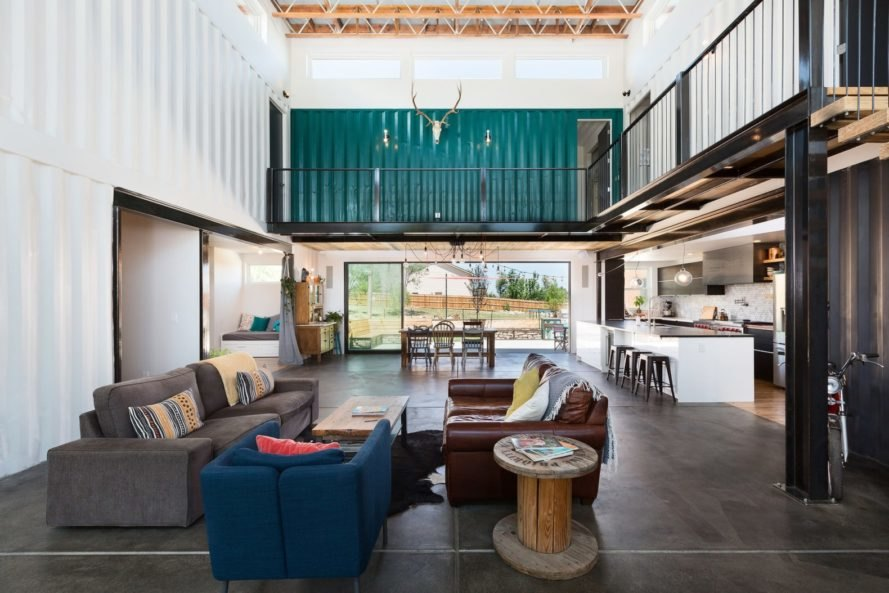 living space with two brown couches, a blue chair and a walkway in the background