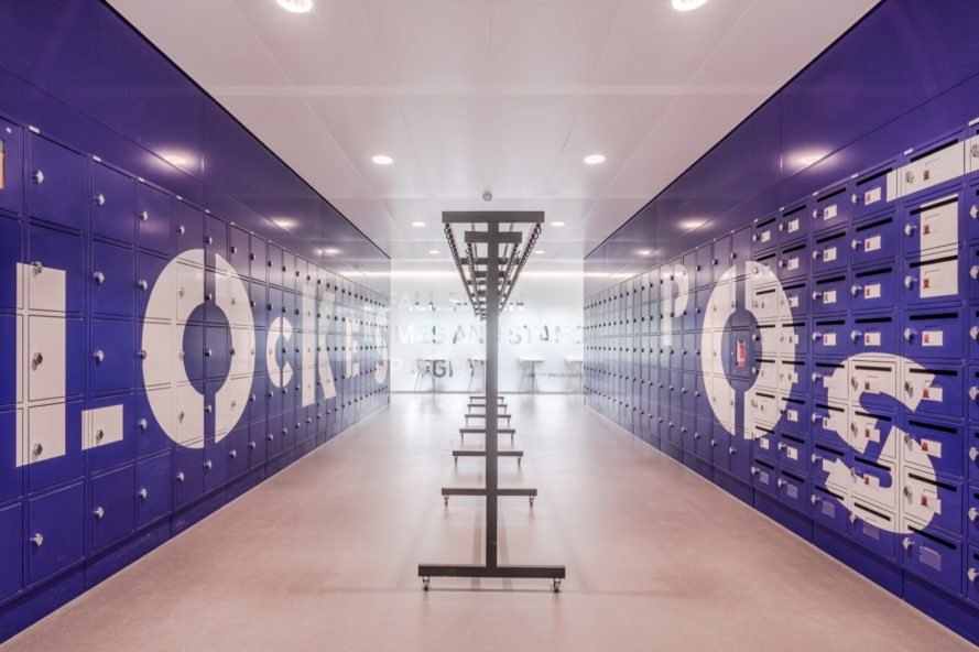 locker room with blue lockers and mailboxes built into the walls