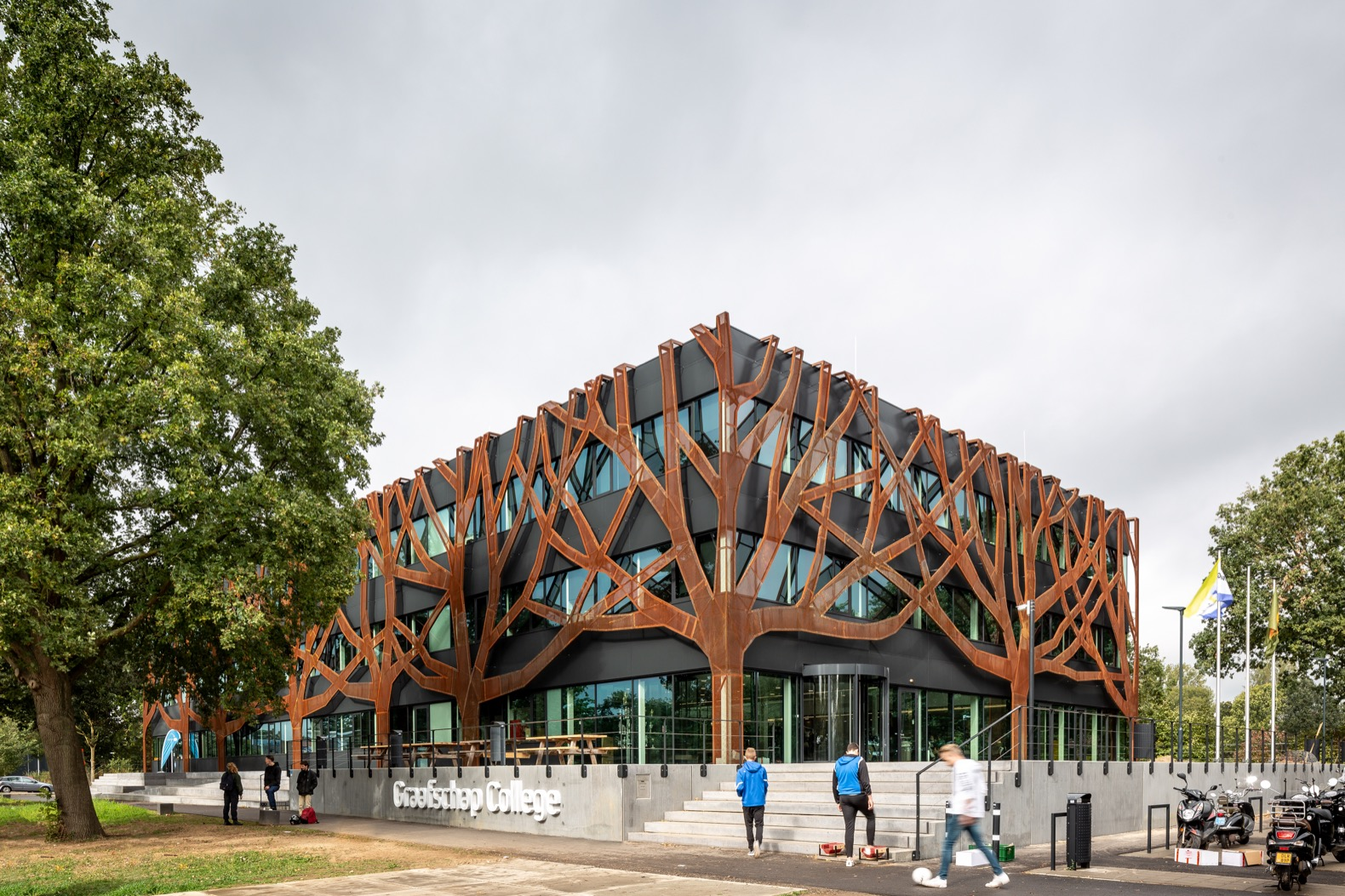 Weathered steel trees wrap around a solar-powered school building