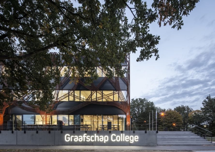 "black building with giant weathered steel tree shapes over the facade and a sign that reads ""Graafschap College"""