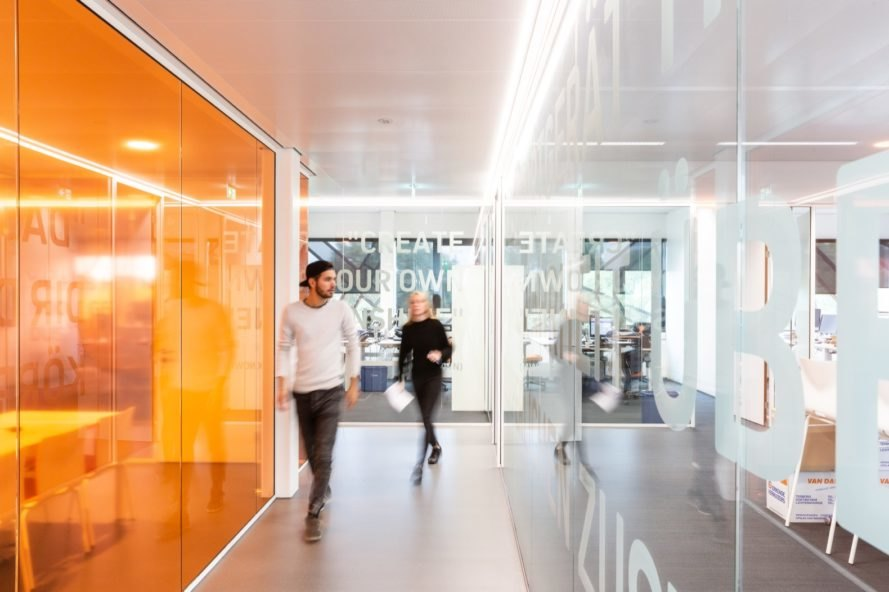 person walking next to a bright orange glass wall