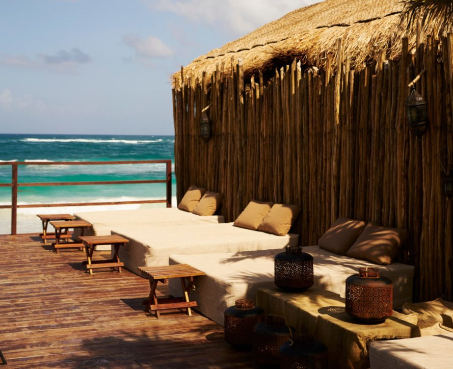 lounge area with chairs next to a beach