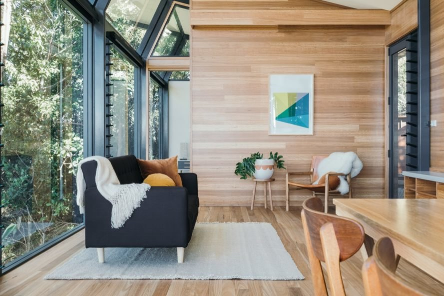 cabin with glass and timber walls and a dark sofa