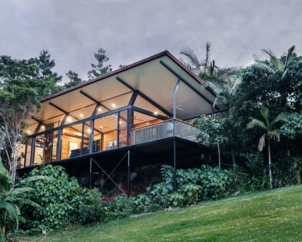 elevated glass cabin surrounded by trees