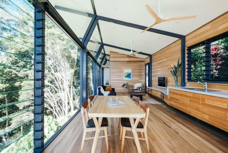 cabin with glass and timber walls and a wood dining table