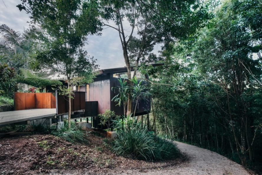 elevated glass and weathered steel cabin in a rainforest