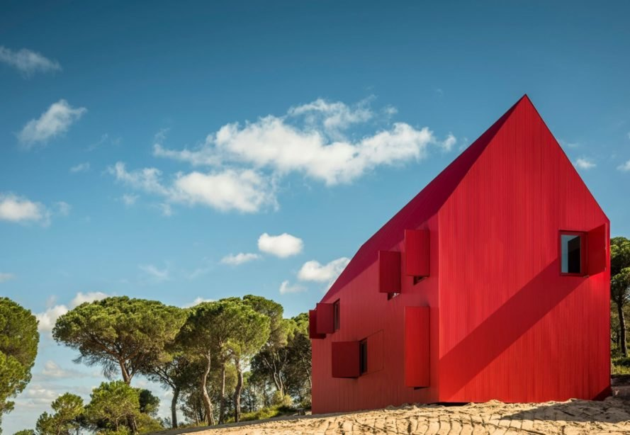 A crimson red home is tucked into a dark green forest in Portugal