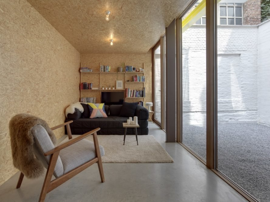 wood room with black sofa and wall of books